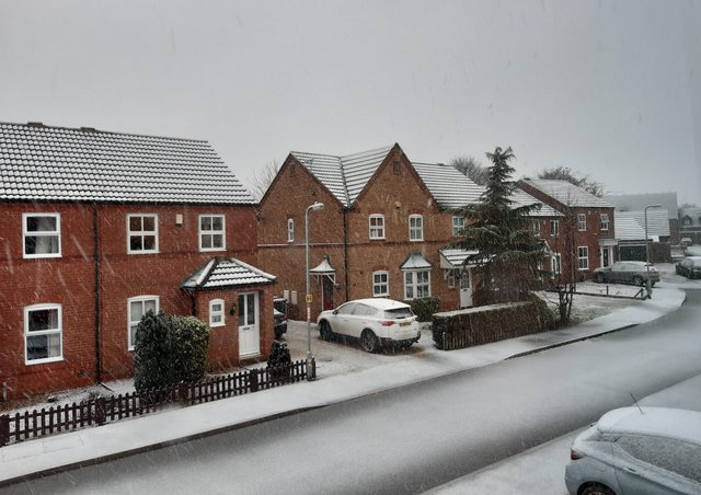 Snow falling and beginning to settle on roads and paths in Sleaford. EMN-210114-102354001
