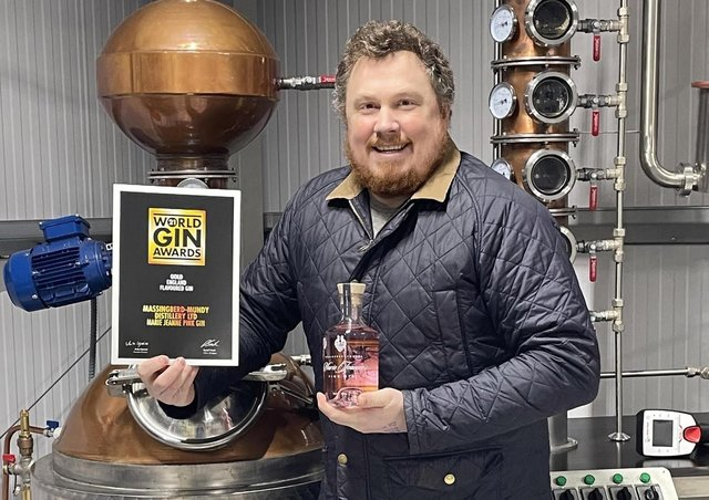 On top of the world: Tristan Jørgensen with his award winning gin - and the certificate to prove it