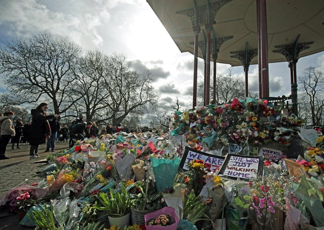 People view floral tributes left at the band stand in Clapham Common, London, after clashes between police and crowds who gathered on Clapham Common on Saturday night to remember Sarah Everard. Serving police constable Wayne Couzens, 48, appeared in court on Saturday charged with kidnapping and murdering the 33-year-old marketing executive, who went missing while walking home from a friend's flat in south London on March 3. Photo: PA EMN-210317-093631001