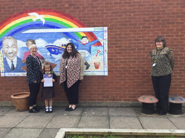 EYFS staff Megan Tory and Leah Dowling with headteacher Mrs Caroline Wellsted and Lily with her certificate.