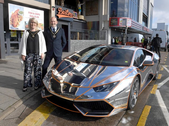 Mayor and Mayoress of Skegness Coun Trevor and Jane Burnham stand by the Lamborghini befire it is hoisted into the new Supercar VIP Lounge in Skegness.