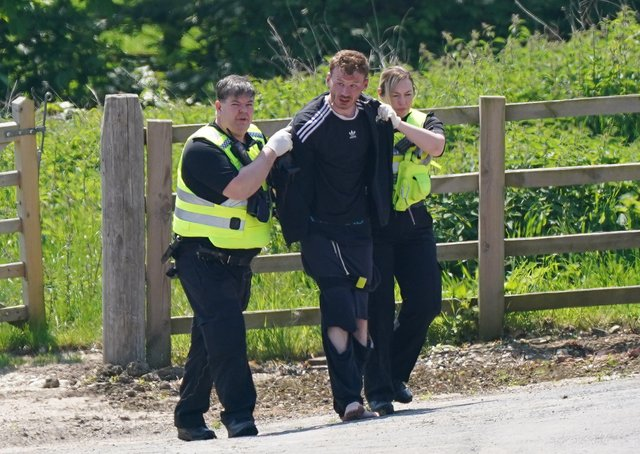 A man is detained at Hallington House Farm, on the outskirts of Louth, Lincolnshire, by officers hunting for Daniel Boulton.Picture: PA Wire