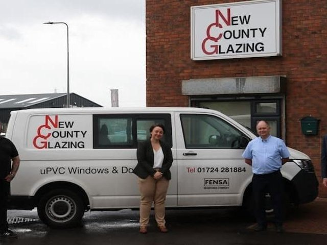 The New County Glazing premises and features from left to right: John Carolan Junior, Scunthorpe MP Holly Mumby-Croft, John Carolan Senior and Councillor Rob Waltham.