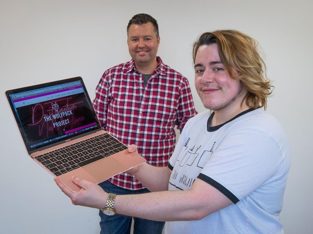 Charity founder Damien Reynolds (back) and employee Alex Inkley (front) with a Wolfpack project laptop
