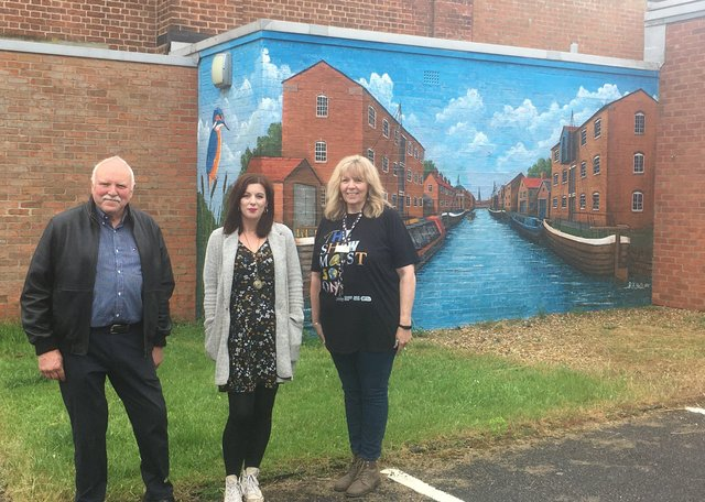 Rob Hall (artist), Sarah Hughes (Lincolnshire One Venues Participation Officer), and Tracey Mackenzie (theatre manager) with the mural