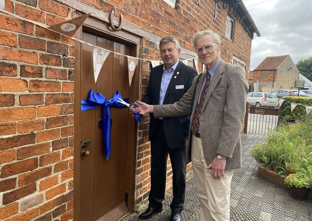 Coun Richard Wright and Malcolm Smith cutting the ribbon to Mrs Smith's Cottage. EMN-210210-141045001
