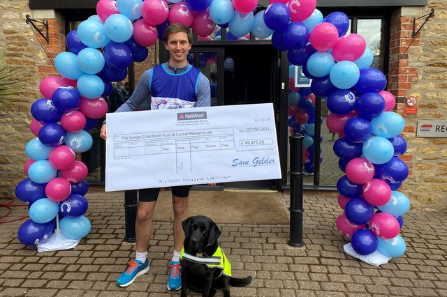 Sam with his dog Tasha and the £49,475.20 cheque